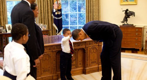 little boy touches obama's head