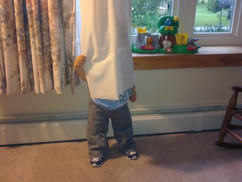 kid hiding behind curtains